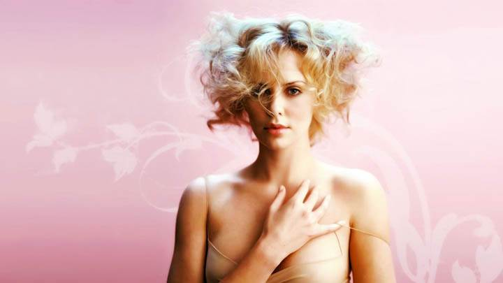 Charlize Theron Hand On Chest Pink Background