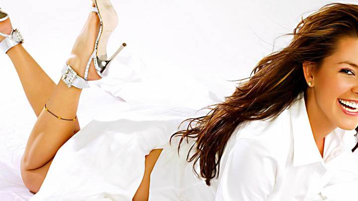 Alicia Machado Laying On Bed Laughing In White Dress