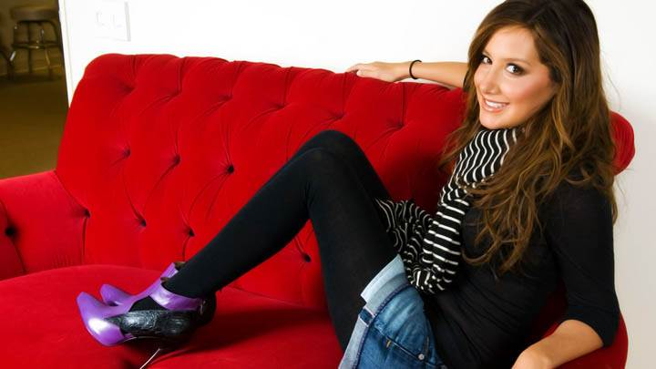 Ashley Tisdale Sitting On Red Sofa & Smiling