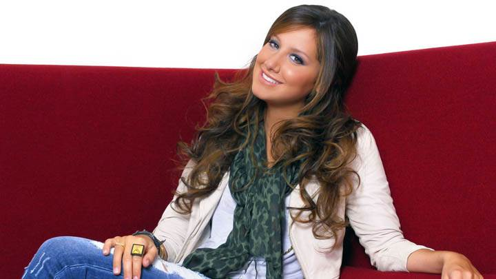 Ashley Tisdale Sitting On Sofa With Blue Jeans And Cream Jacket