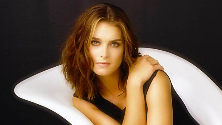Brooke Shields Sitting On White Sofa Wearing Black Dress