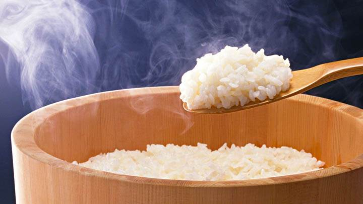 White Rice With Steam in Wooden Cooker