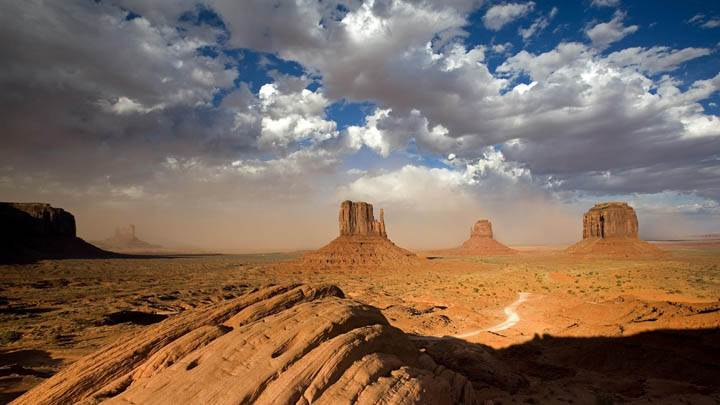 A Building Sandstorm Behind the Two Mittens, Monument Valley, Utah
