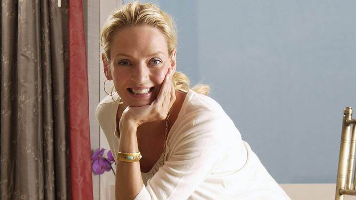 Uma Thurman Smiling & Sitting On Golden Chair