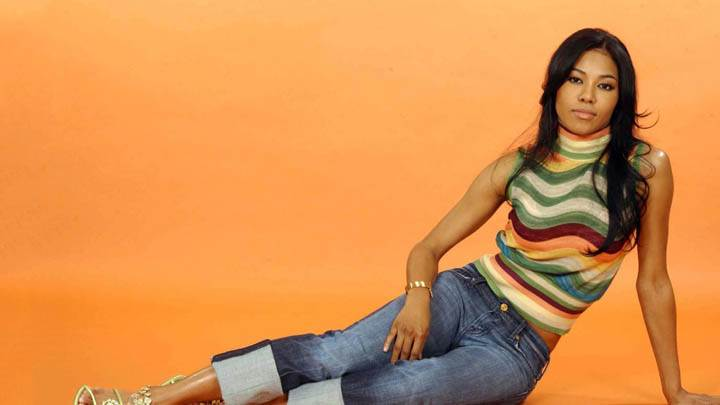 Amerie In Colorful Top N Blue Jeans Sitting Pose