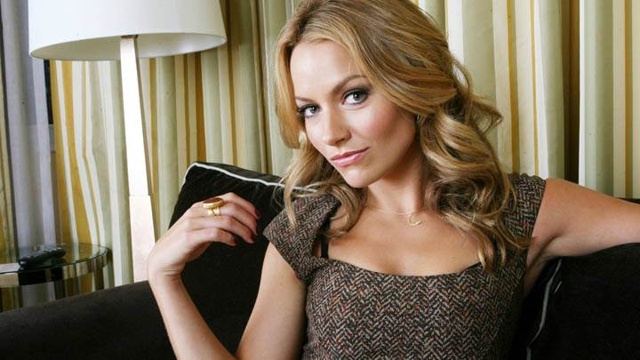 Becki Newton Sitting on Sofa And Smiling