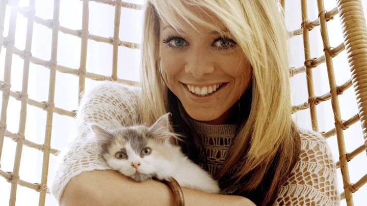 Liz McClarnon Smiling Face & White Cat in Hand