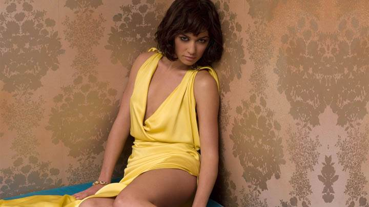 Olga Kurylenko – Sitting Pose in Yellow Dress