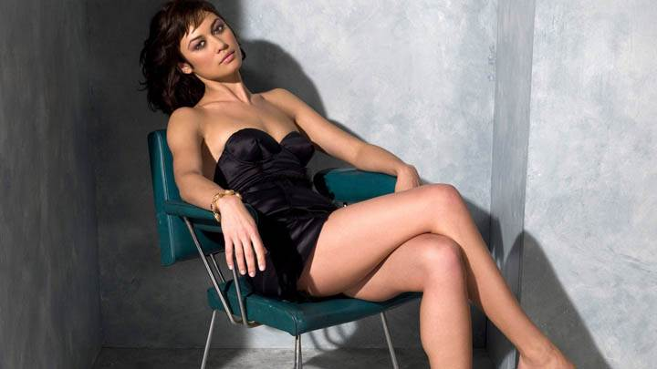 Olga Kurylenko Sitting on Chair In Black Dress