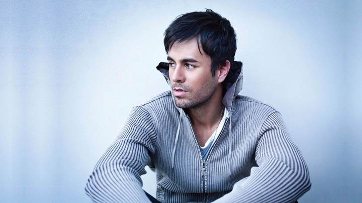 Enrique Iglesias Sitting Pose Blue Background
