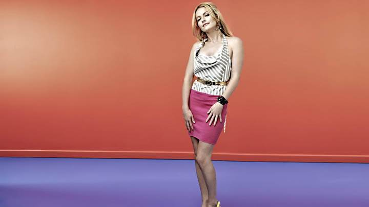 Becki Newton Modeling Pose in Orange & Purple Background