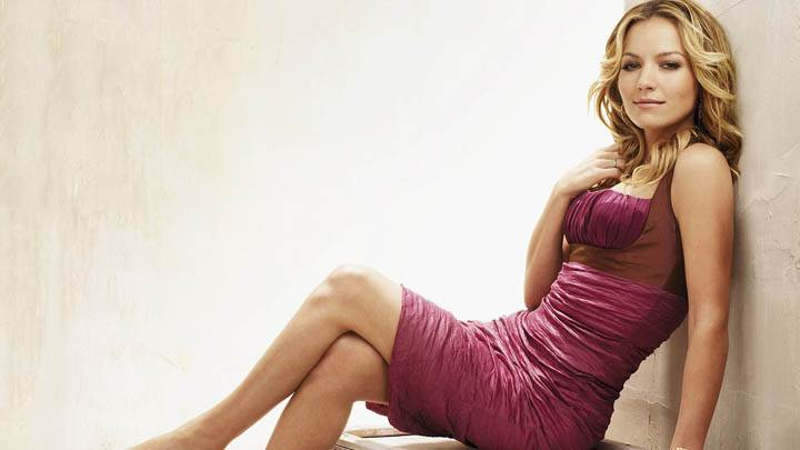 Becki Newton Sitting Pose in Pink Dress
