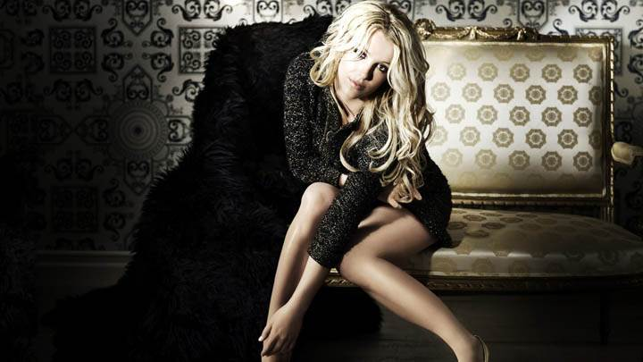 Britney Spears Sitting on Golden Sofa in Black Dress