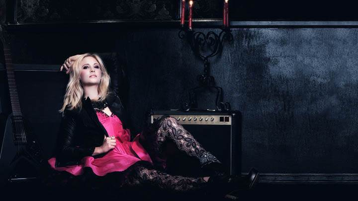 Candice Accola Sitting Pose in Black & Pink Dress