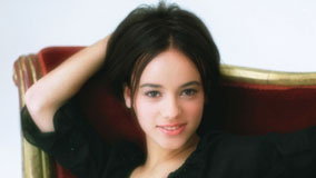 Alizee Jacotey Sitting On Red Sofa In Black Dress