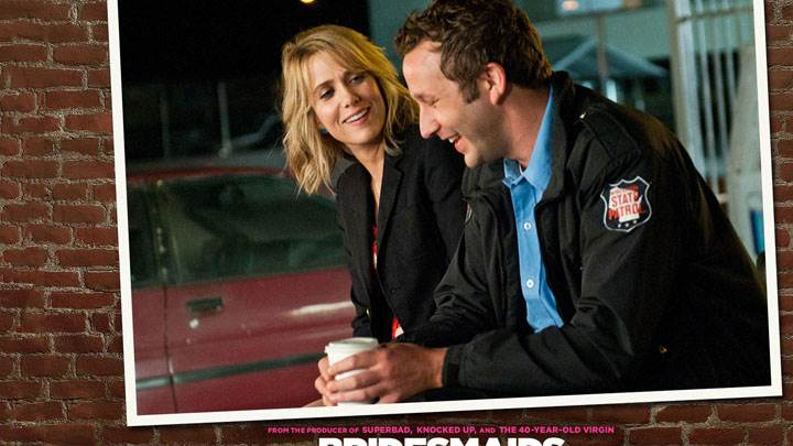 Bridesmaids – Kristen Wiig And Chris O'dowd Smiling And Sitting Side View
