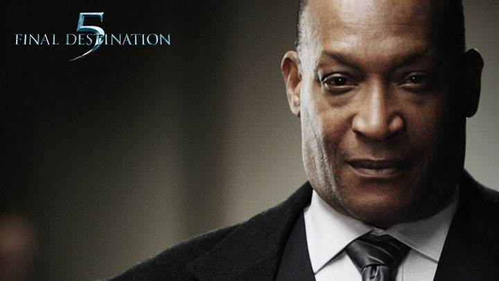 Final Destination 5 – Tony Todd Smiling In Black Coat