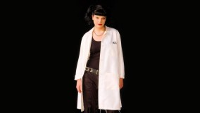 Abby Sciuto Smiling In White Coat And Black Background