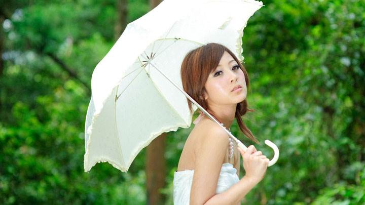 Asian Girl Thinking With White Umbrella in Green Garden