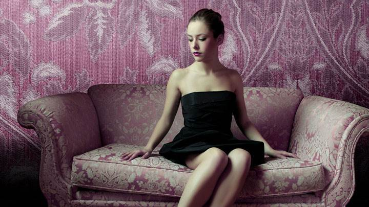 Beautiful Chinese Girl in Black Dress Sitting On Purple Sofa