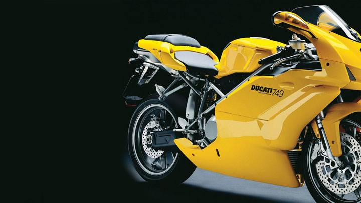 ducati 749 2005 in yellow side pose and black background wallpaper