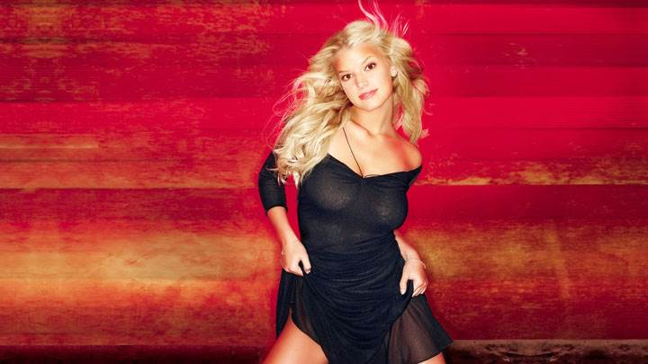 Jessica Simpson Smiling Naughty Pose In Black Dress And Red Background
