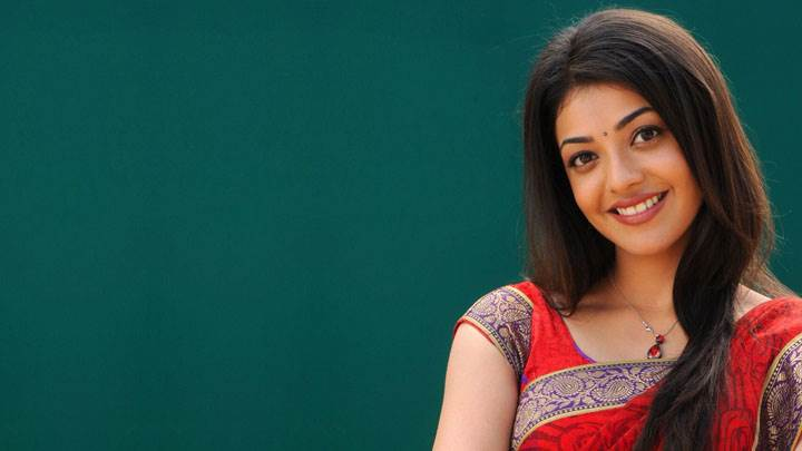 Kajal Aggarwal Smiling In Red Saree And Green Background