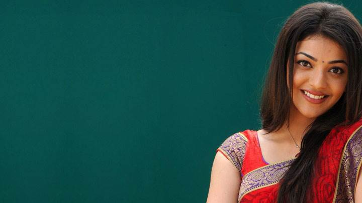 Kajal Aggarwal Smiling In Red Saree And Looking Front