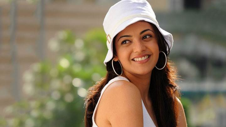 Kajal Aggarwal Smiling In White Top And Cap And Long Earings