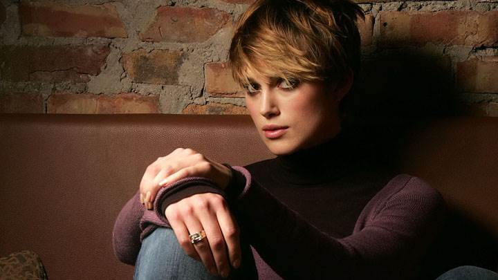 Keira Knightley Sitting In Brown Top And Blue Jeans Looking Front