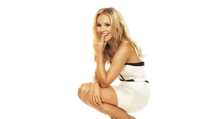 Kristen Bell Smiling Sitting Pose In White Dress And White Background