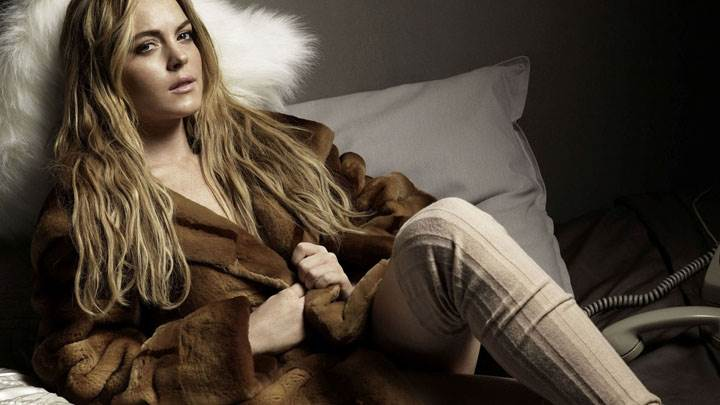 Lindsay Lohan Sitting Pose In Brown Long Coat On Bed