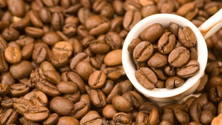 Lots of Coffee Beans And Beans in Cup Closeup
