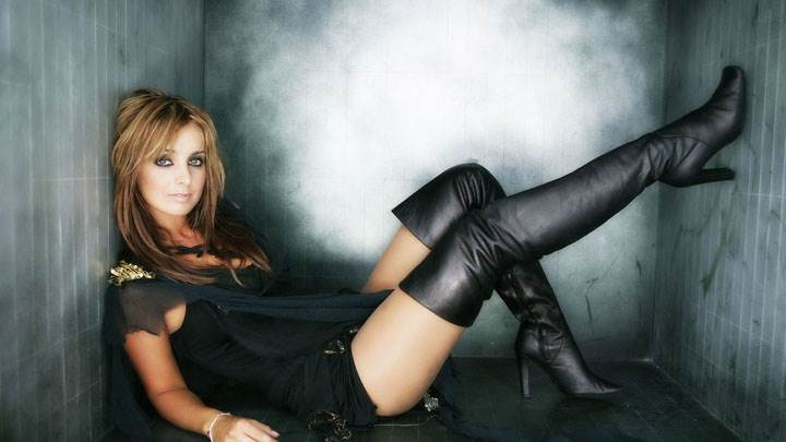 Louise Redknapp Looking Front In Black Dress Sitting Pose