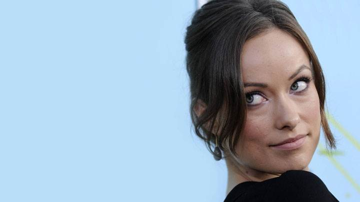 Olivia Wilde Looking Back In Black Dress And Blue Background
