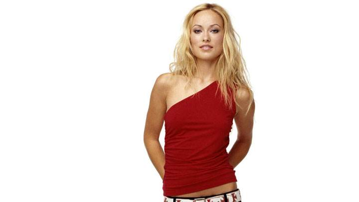 Olivia Wilde Smiling in Red Top And Black Jeans And White Background
