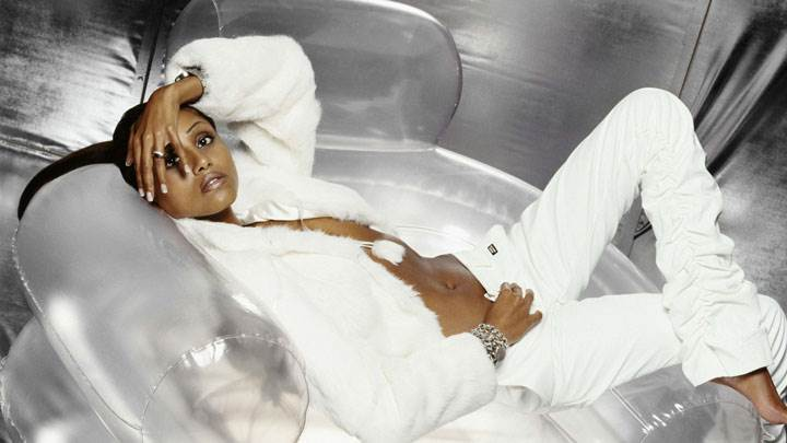 Sabrina Setlur Laying On Silver Sofa In White Dress