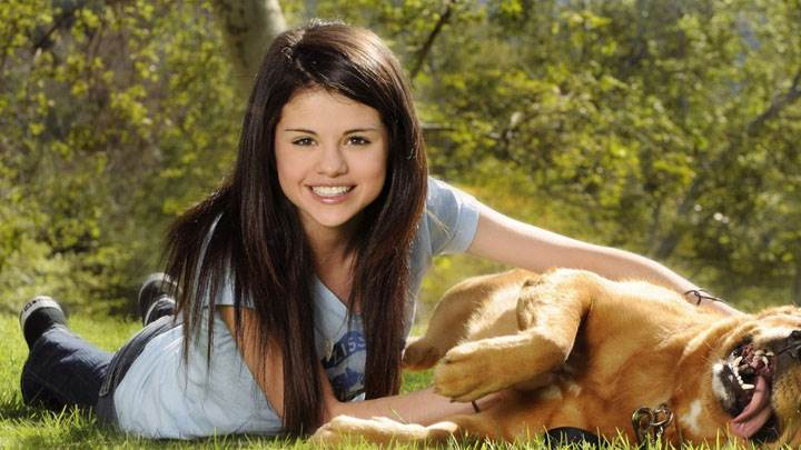 Selena Gomez Playing Laying Pose With Dog In Garden