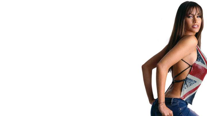 Sofia Vergara Smiling In Top And Blue Jeans And White Background