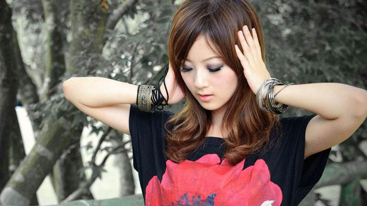 Sweet Pose Of A Asian Girl Closed Eyes And Black Flower Top