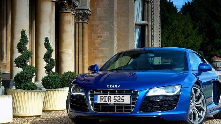 Front Pose Of 2009 Audi R8 V10 Outside House In Blue Wallpaper