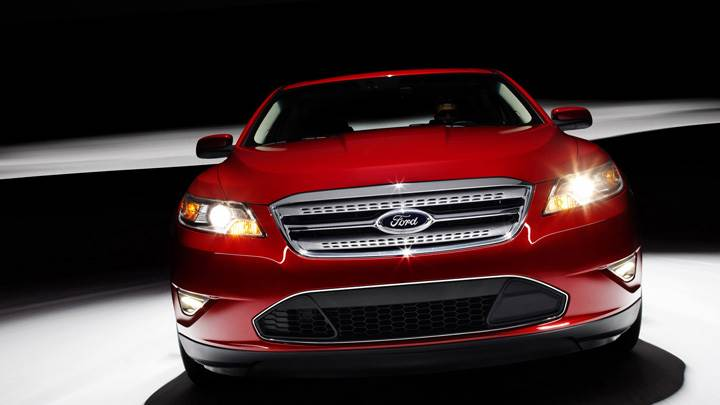 Front Pose of 2010 Ford Taurus SHO In Red N HeadLights On