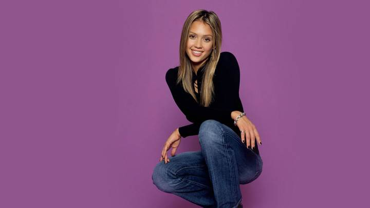 Jessica Alba Smiling In Black Top N Blue Jeans Sitting Pose