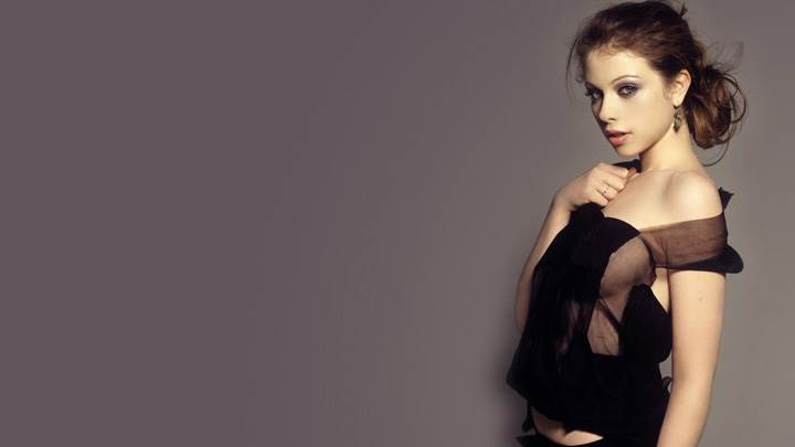 Michelle Trachtenberg In Black Top Side Pose Standing With Wall
