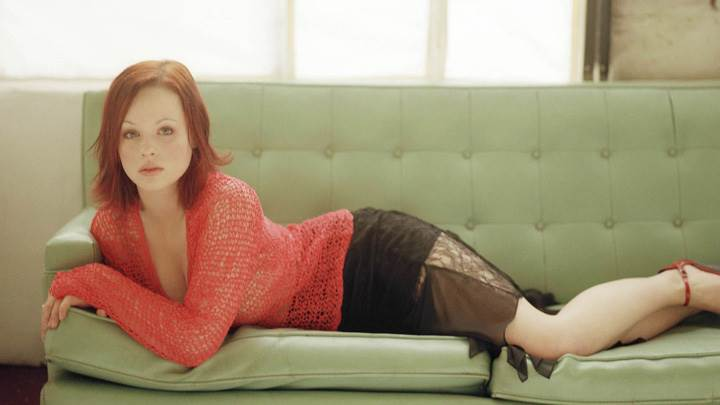Thora Birch Laying Pose On Sofa In Red Transparent Top
