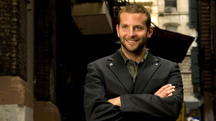 Bradley Cooper Smiling In Black Coat Outside Building
