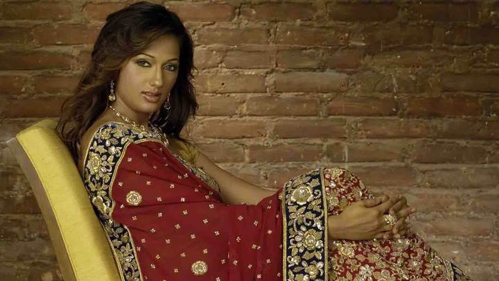 Brinda Parekh Sitting In Red Heavy Work Lehenga Side Pose