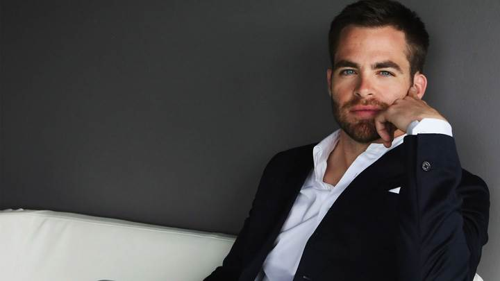 Chris Pine Looking At Camera In Black Coat Sitting Pose