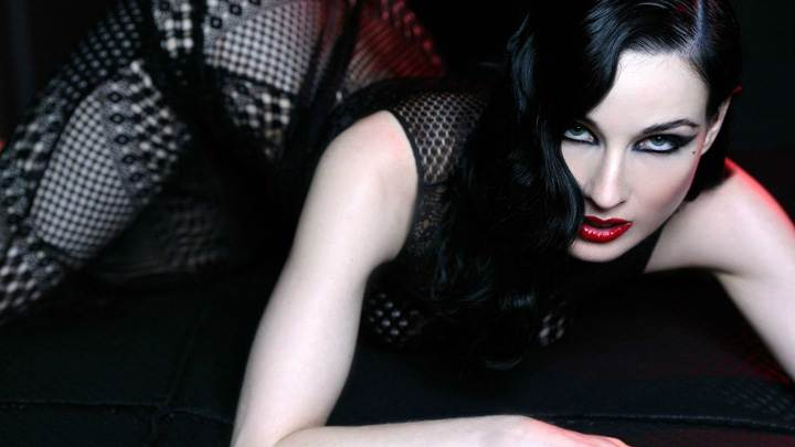 Dita Von Teese Red Lips Laying Pose In Black Dress Looking At Camera