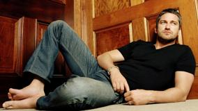 Gerard Butler In Black T-Shirt N Blue Jeans Sitting Pose
